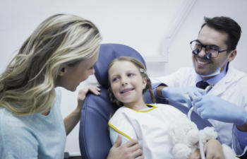 A restorative dentist talking to a mother assisting her liitle daughter sitting in a dental chair.