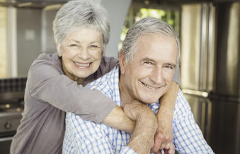 A senior couple showing their nice teeth in their smiles.