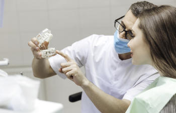 A dentist with a dental model explaining the pros of custom abutments to a woman in a dental chair.