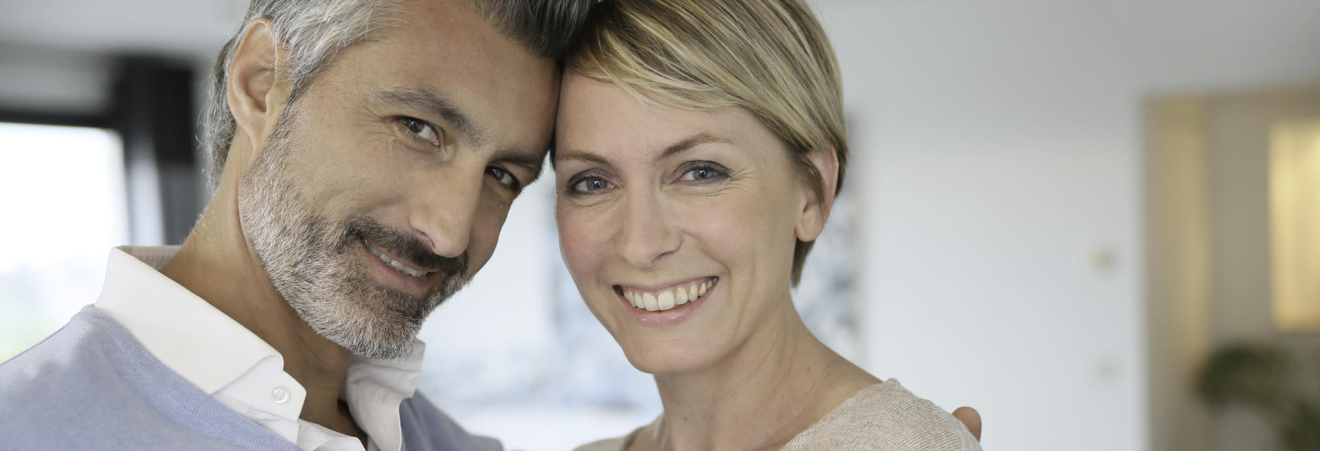 smiling middle-aged couple showing beautiful teeth in their smiles