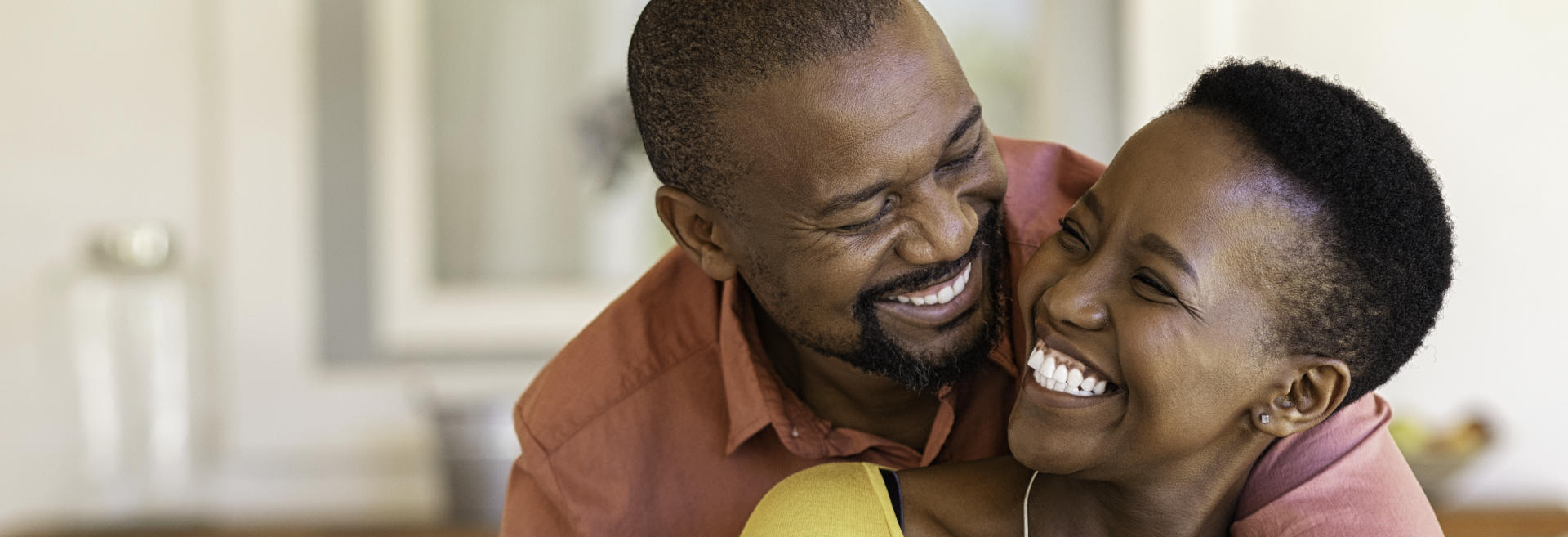 Happy middle-aged Afro-American couple showing perfect teeth in their smiles