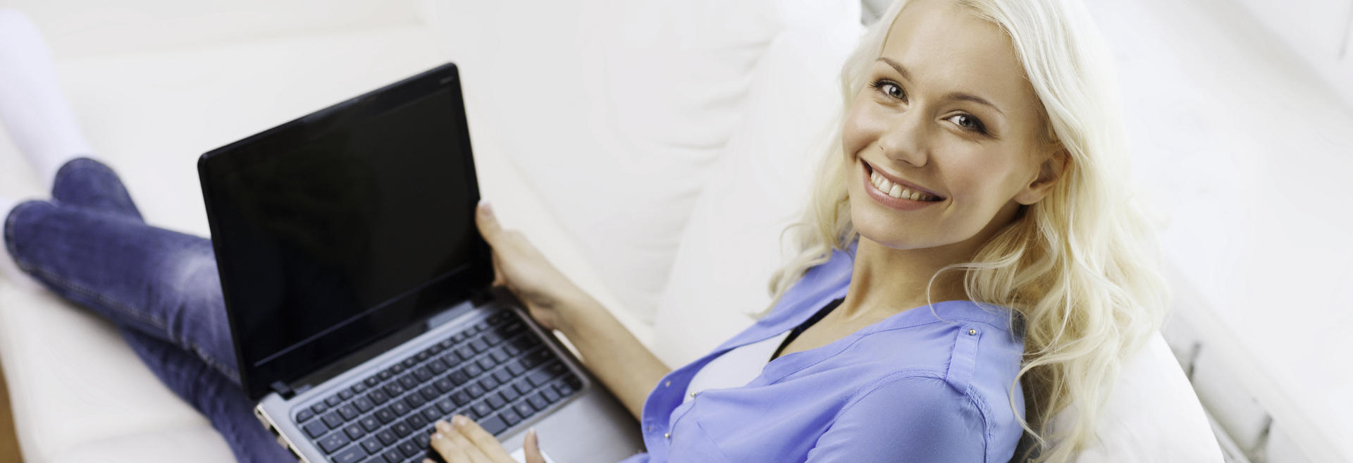 broadly smiling beautiful young woman with laptop