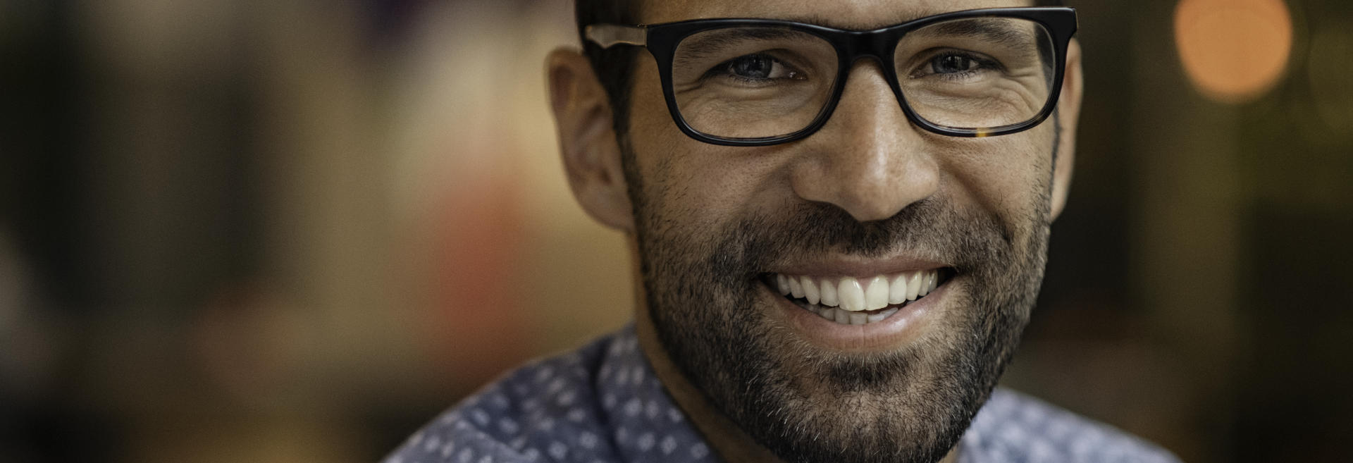 A happy middle-aged man wearing glasses showing beautiful teeth after full mouth reconstruction in his smile.
