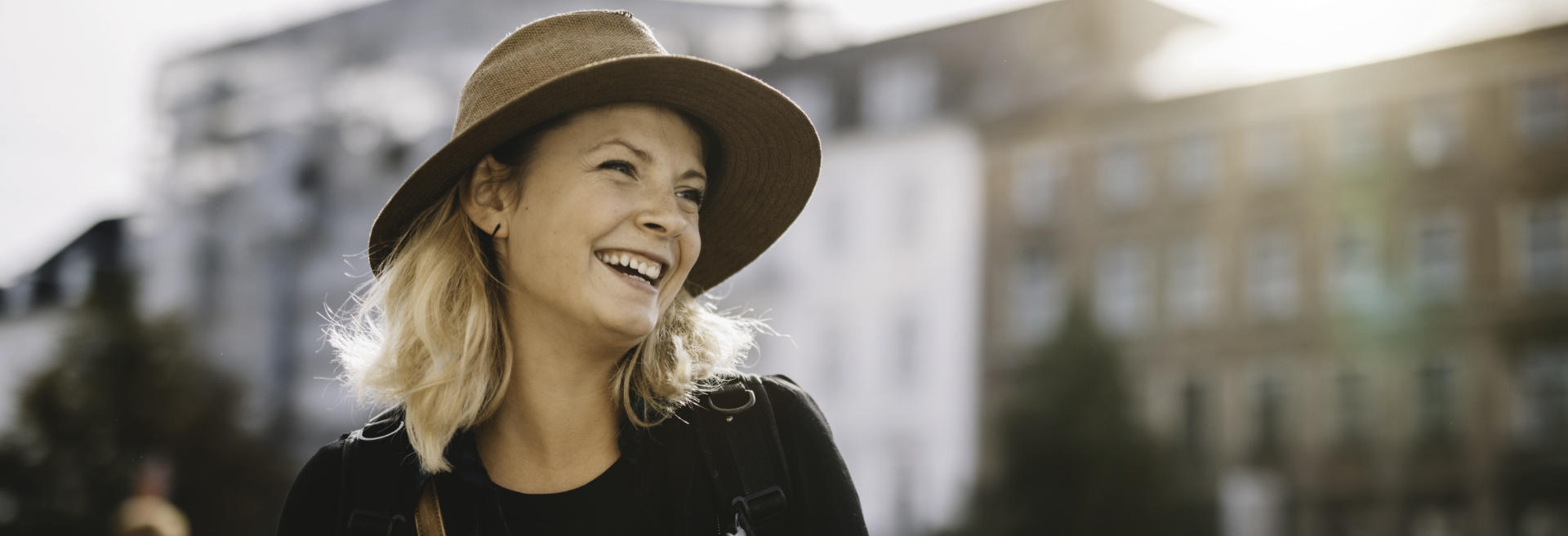 broadly smiling woman with hat sightseeing a city