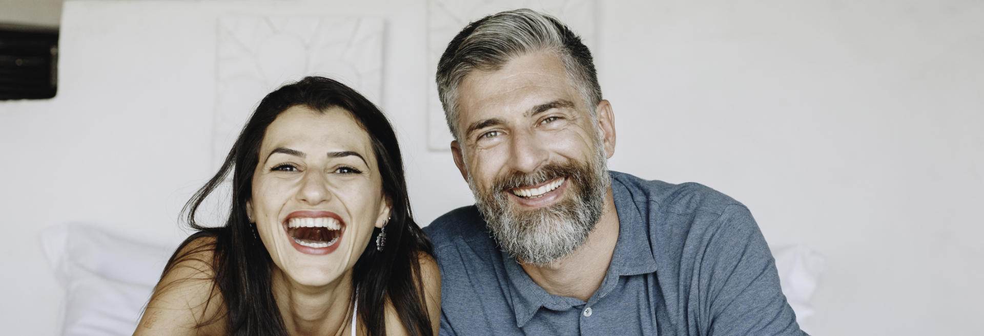 happily smiling middle-aged couple showing perfect teeth in their smiles